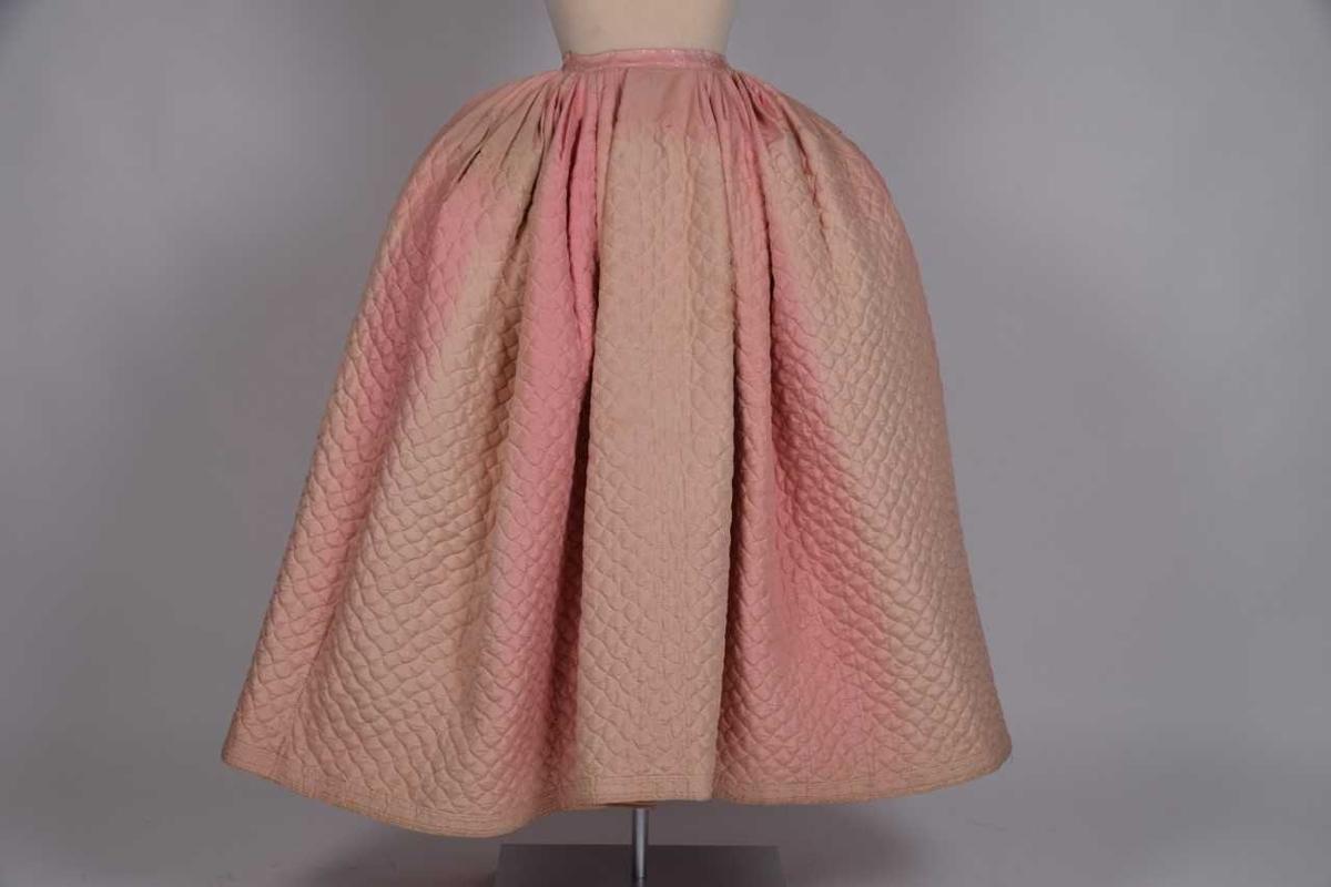 a.) Kjol av rosa siden. Matlasserad, med sticksöm. b.) Tröja av vitt siden, sidenfodrad. Runt halsringningen krage av knypplade spetsar. Knyts framtill ihop med sidenband.  Har tillhört givarens förfäder.