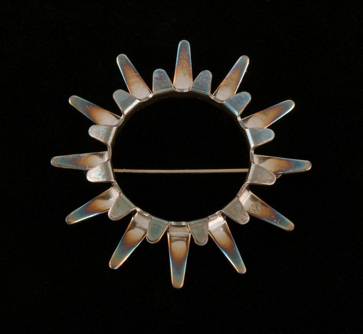 Blankpolert brosje stanset ut av en sølvplate og bøyd i form av en sirkulær stilisert sol, bestående av en ytre og en indre flikekrans. Flikene er bøyd slik at 13 korte fliker fyller mellomrommene mellom 13 lange fliker. Nålen er loddet på baksiden.