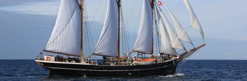 Sort seilbåt med tre master og fulle seil, mot blått hav og blå himmel.