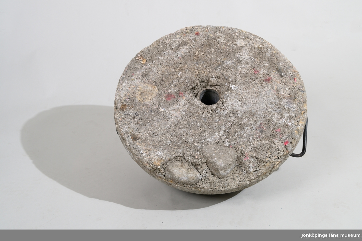 """Insamlingsbössa, """"Julgryta"""", använd av Frälsningsarmén för insamling av pengar. Insamlingsbössan består av en upphängningsanordning i form av en stående stång (metallrör), monterad i en betong-/cementfot. Stången är på mitten utböjd för att ge plats åt en metallgryta med rött lock, hängande i tre kedjor. Locket har en skåra för inkast av pengar. Grytan är låsbar genom ett hänglås under botten. Lås saknas för att låsa fast kedjorna vid stången. Upptill sitter en dubbel skylt med information om Frälsningsarméns julinsamling. På toppen av stången sitter två löstagbara flaggor med Frälsningsarméns emblem. Se vidare Historik.  JM 56619:1, Stång av rödfärgat metallrör, utböjd på mitten. På toppen av röret finns två mindre rör som är flagghållare. Längst ner på stången sitter en pappersremsa med tryckt text: """"STOCKHOLM 6"""".  JM 56619:2, Fot till stång, rund form av gjuten betong/cement, har stånghållare i mitten och två handtag av järn.  JM 56619:3, Gryta av aluminium med fastmonterat rött lock (insamlingsbössa). Locket har skåra för inkast av pengar. Under botten hänger ett lås. Under botten är skrivet med svart tusch: """"24"""", """"6:an"""". Grytan hänger i tre kedjor.  JM 56619:4a-b, Informationsskyltar, 2 st, fastskruvade på stången och mot varandra med två vingmuttrar. Skylten är gjord av masonitskiva (träfiberskiva) med påklistrat gult papper med tryckt text: """"FRÄLSNINGSARMÉNS JULINSAMLING"""", """"Du kan hjälpa behövande mitt ibland oss eller de som drabbas vid katastrofer."""", """"FRÄLSNINGSARMÉN"""", """"HÅLL GRYTAN KOKANDE"""".  JM 56619:5a-d, Flaggor, 2 st rektangulära av konstmaterial, med 2 st tillhörande träpinnar/rundstavar. Flaggan är tryckt med röd botten, blåa kanter och gul stjärna i mitten. I en kortsida är en vit kanal sydd för att trä in en träpinne i, för att fästa flaggan i upphängningsstångens topp. En av rundpinnarna är lagad med tejp."""