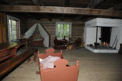 Interiørbilde fra Grimsrudbygningen, her sto langbord med benker, veggfast seng med forheng, vugge og peis i samme rom.