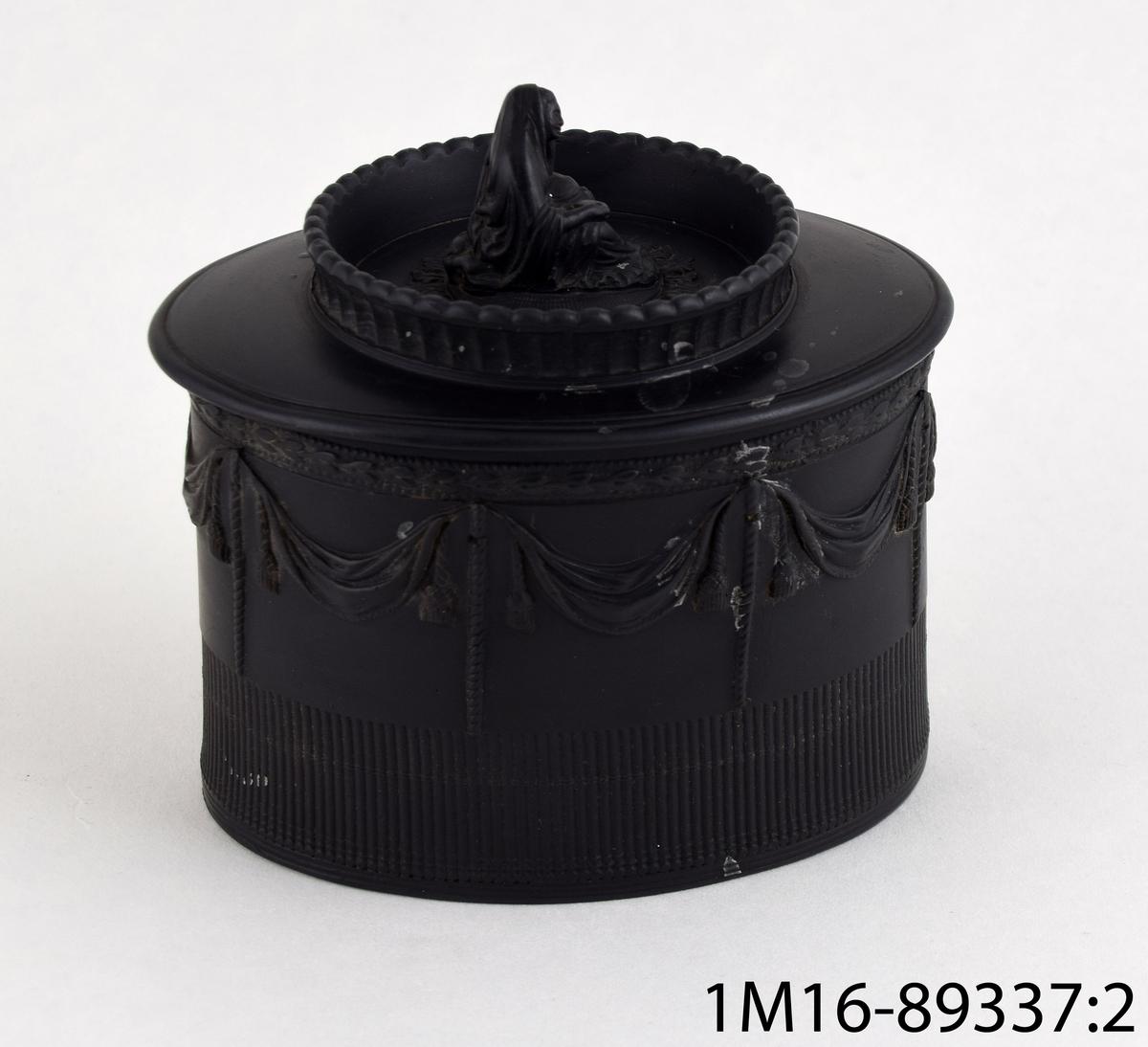 """Sockerskål av basaltware, det vill säga oglaserat svart stengods av engelsk tillverkning. Det tillhörande locket har en knopp i form av en sittande kvinna iförd slöja, formen kallas """"widow shape""""; det föreställer en änka. Dekoren är detaljerad och inspirerad av antika original. Troligen tillverkad av Neale & Co., Hanley, Staffordshire, England."""