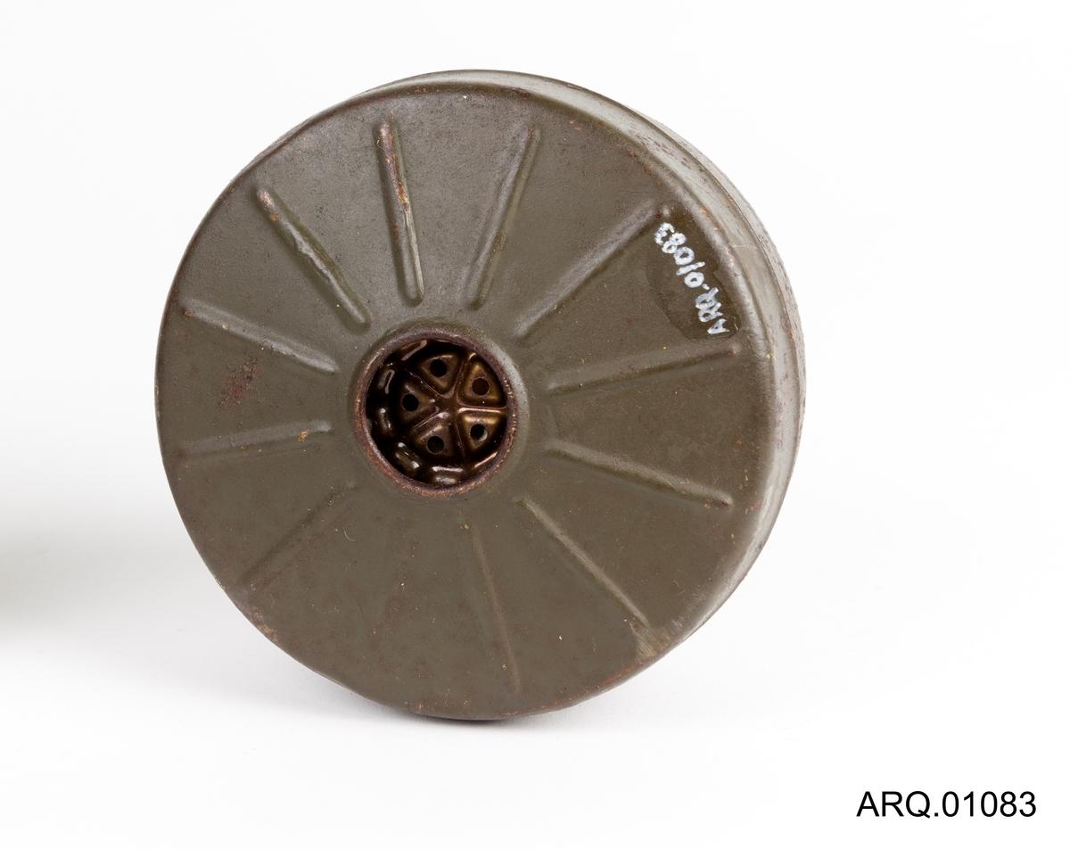 Filterpraton (gummifilter) for beskyttelse mot gass/røyk. Festes på gassmasken ved å skru inn gjengene. Lakkert; Mørk grønn/Grå i fargen. Dette filteret har ikke bevart det lille lokket ved gjengene, men har et beskyttelseslokk i bunnen. Ekstra filterpatron kunne fraktes i oppbevaringboksen til gassmasken.