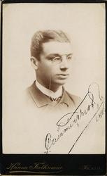 Foto av en ung man med pincené, klädd  i kavajkostym med stä