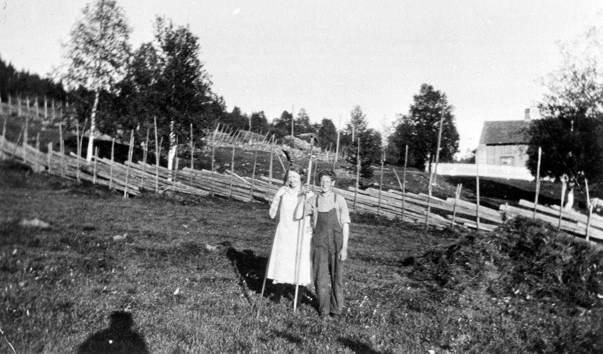 Høyonn med river, Sveinhaug, Furnes, Ringsaker. Eli Frydenlund (1903-1994), Erling Svenhaug (1912-1983). Fotografert på Svenhaug (Gnr 721, Bnr 14) under Vestre Høsbjør i 1927.