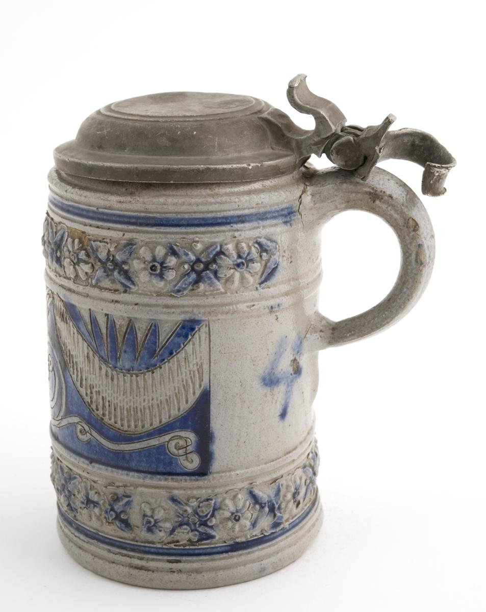 """Krus i grå keramikk av en type som stammer fra Westerwald-området i Tyskland. Karakteristisk er risset og stemplet dekor og pålagte relieffer, farget med koboltblått og senere også manganfiolett, under klar saltglasur. Dette lave, sylinderformete kruset kalles """"Humpen"""" og ble masseprodusert gjennom hele 1600 og 1700-tallet. Lokk i metall."""