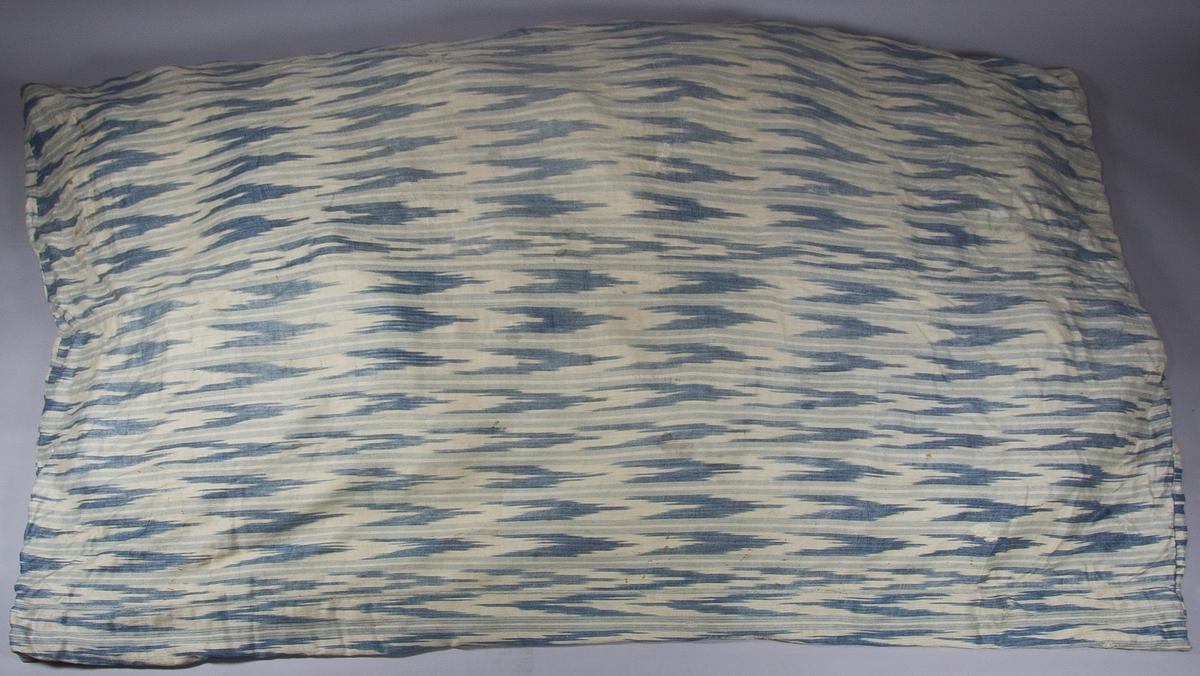 Bolster, tillverkat av handvävt linnetyg, vävt i kypert. Varpen mönstrad med både ränder och flamgarnsränder, i ljusblått och blått på vit botten. Inslag vitt. Fem våder hopsydda runtom.  Fyllning: fjäder.