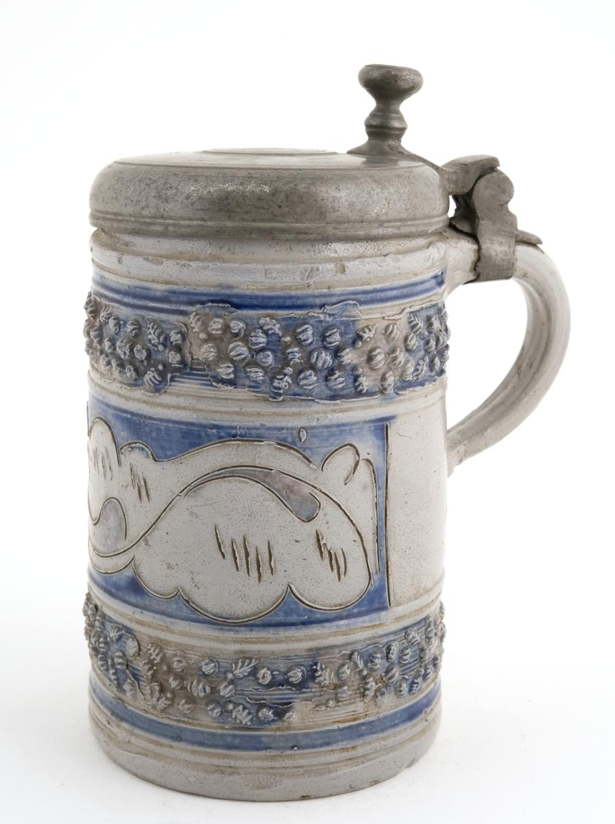 """Krus i grå keramikk av en type som stammer fra Westerwald-området i Tyskland. Karakteristisk er risset og stemplet dekor og pålagte relieffer, farget med koboltblått og senere også manganfiolett, under klar saltglasur. Dette lave, sylinderformete kruset kalles """"Humpen"""" og ble masseprodusert gjennom hele 1600 og 1700-tallet."""
