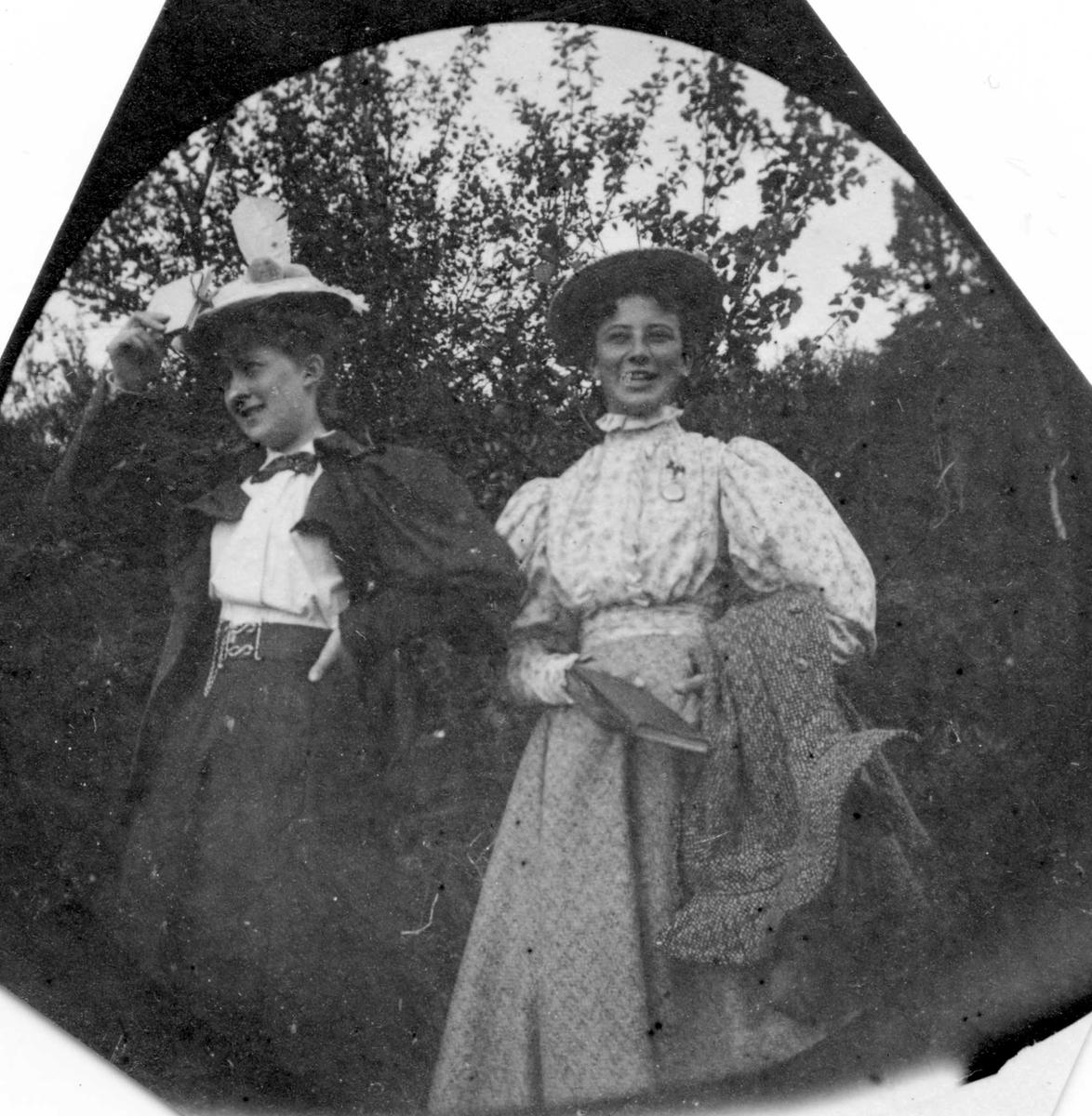 To damer i skogen, ei holder ei bok i hånden.